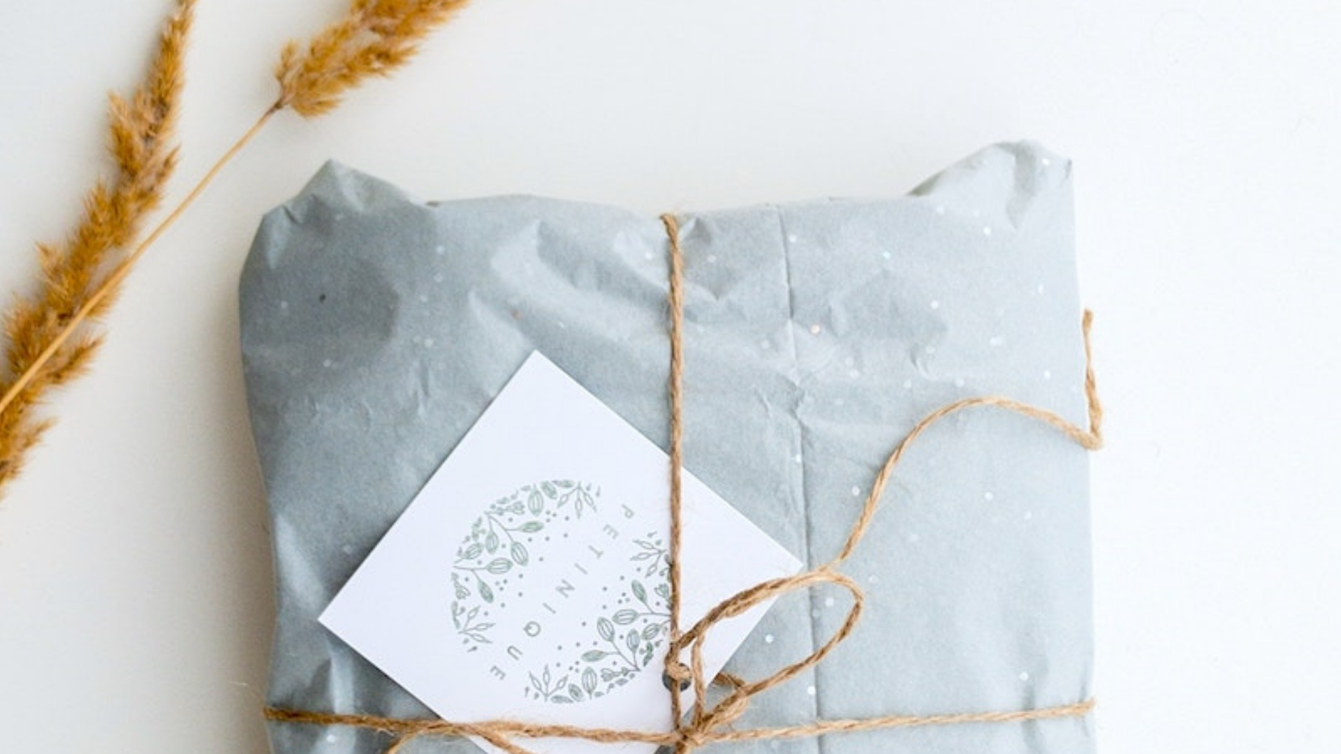 Cropped shot of pale blue parcel with twine and white gift tag.